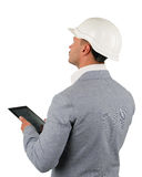 Young architect or engineer doing an inspection. Making comparisons against information on his tablet computer, angled profile view from behind on white Royalty Free Stock Photo