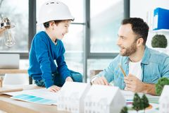 Young architect explaining his project to little son. Simple explanation. Pleasant bristled architect explaining the key ideas of his project to his son while Stock Photos