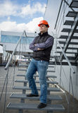 Young architect in hard hat posing on metal staircase Royalty Free Stock Photos