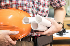 Young architect holding blueprint and hamlet. In office renovation, architecture contractor developer and renovation concept Stock Image