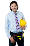 Young architect holding hard hat Royalty Free Stock Images