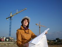 Young architect looking at blueprint against crane Stock Photos