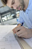 Young architect making new designs. Architect designing on drafting table Royalty Free Stock Image