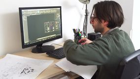 Young architect male working in office on desk, types on a laptop, blueprints laying on his desk