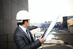 Young architect pointing building. Young architect with white helmet holding blueprint and clipboard pointing at the building construction Royalty Free Stock Image