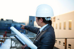 Young architect pointing at the building construction. Young architect with white helmet holding blueprint and clipboard pointing at the building construction Stock Image