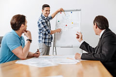 Young architect pointing at the printout on whiteboard. Important remarks. Pleasant cheerful young architect standing near the whiteboard and pointing at the stock photography