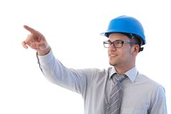 Young architect pointing to distance smiling. Young architect at construction site pointing to distance, smiling Royalty Free Stock Images