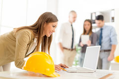 Young Architect. Smiling young female architect analyzing project at laptop in office. Her colleagues standing in background Royalty Free Stock Photos