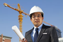 Young architect standing front of a building site. Young asian architect wearing a protective helmet standing under construction with yellow crane and blue sky Royalty Free Stock Photo