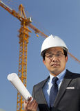 Young architect standing under yellow crane building site. Vertical image. Young asian architect wearing a protective helmet standing under construction with Royalty Free Stock Image