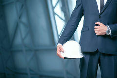 Young architect in suit is carrying a hardhat Royalty Free Stock Photo