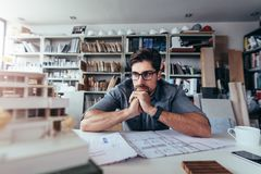 Young architect thinking about new construction ideas. Young architect looking at architecture house model and thinking about new ideas. Male designer sitting in stock photo