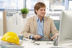 Young architect using drawing pad. Young architect sitting at office desk, drawing pad, looking at screen stock images
