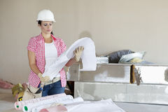 Young architect wearing hardhat looking building plans royalty free stock image