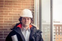 Young architect with white helmet holding blueprint and smiling look at the camera. Soft focus, toned. Young architect with white helmet holding blueprint and Royalty Free Stock Photo