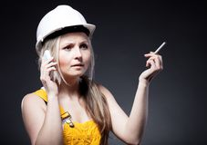 Young architect woman construction worker, cigarette and phone Royalty Free Stock Images