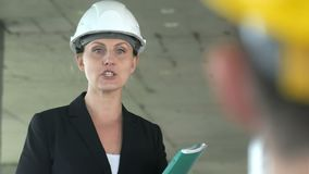 A young architect woman working on construction site, talking with her colleague stock video