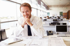 Young architect at work in an office, smiling to camera Stock Photography