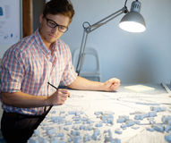 Young architect working on drawing table in architect  studio. Young architect working on drawing table in architect studio Royalty Free Stock Image