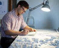 Young architect working on drawing table in architect  studio. Royalty Free Stock Images