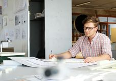 Young architect working on drawing table in architect  studio. Young architect working on drawing table in architect studio Royalty Free Stock Photo
