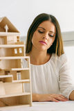 Young architect working on a wooden model Royalty Free Stock Images