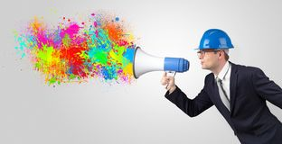 Young architect yelling with megaphone and colorful splash concept. Young architect constructor yelling with megaphone with and colorful splash concept royalty free stock photo
