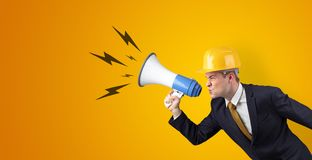 Young architect yelling with megaphone. Young architect constructor yelling with megaphone and copyspace royalty free stock photography