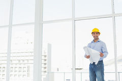 Young architect in yellow hard hat with blueprint in office. Portrait of a young architect in yellow hard hat with blueprint in a bright office Stock Images