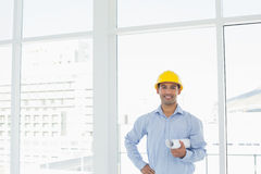 Young architect in yellow hard hat with blueprint in office. Portrait of a smiling young architect in yellow hard hat with blueprint in a bright office Royalty Free Stock Images