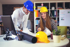 Young architects discussing construction plans in off Stock Photos