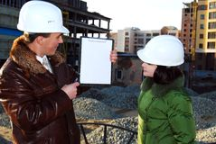 Young architects looking at blueprint. Stock Images