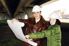 Young architects looking at blueprint. Royalty Free Stock Photos