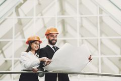 Young architects looking at blueprint in front of construction site. Royalty Free Stock Images