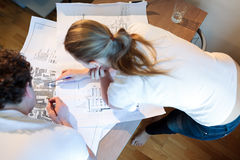 Young architects working with map and blueprint Royalty Free Stock Photo