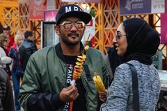 A young Arezbijian couple in hijab and glasses eating potato chips on a stick. Street food of Azerbaijan royalty free stock photos