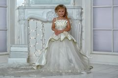 Young aristocrat in a smart white dress. In a Christmas royalty free stock image