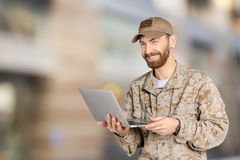 Young army soldier with a laptop Stock Images