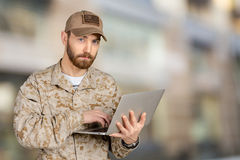 Young army soldier with a laptop Royalty Free Stock Images