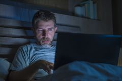 Tired and stressed workaholic man working late night exhausted on bed busy with laptop computer feeling sleepy suffering business royalty free stock image