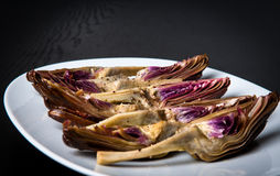 Young artichoke antipasti. On a white plate and dark background Royalty Free Stock Images