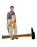 Young artisan in overallst. Young artisan in overalls standing with giant hammer at his feet stock photos