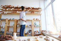 Choice of earthenware. Young artisan taking clay mug from upper shelf in his workroom Stock Image