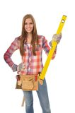 Young artisan with a yellow spirit level. Attractive young artisan holds a spirit level Royalty Free Stock Image