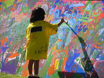 Young artist. A young girl painting on a big canvas Royalty Free Stock Images