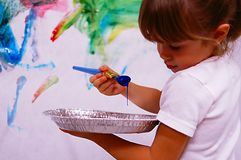 Young artist. A young girl painting a picture on the wall stock photo