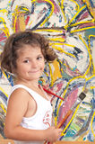 Young Artist. Young girl with a captivating personality in front of an abstract painting royalty free stock image