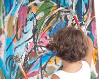 Young Artist. Young girl with a captivating personality in front of an abstract painting stock photo