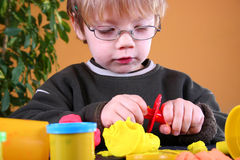 Young Artist. Young cute boy playing with plasticine Stock Images